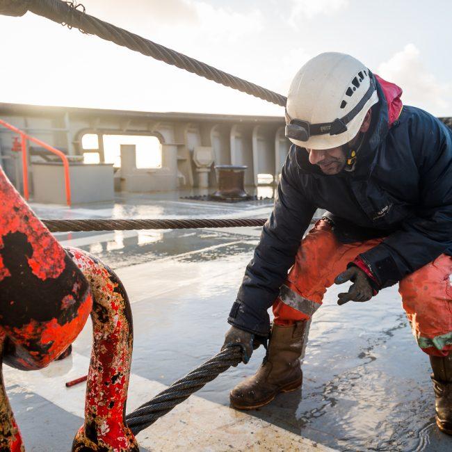 Un membre de l'équipage du remorqueur d'intervention, d'assistance et de sauvetage (RIAS) Abeille Bourbon prépare le câble de remorquage en plage arrière.